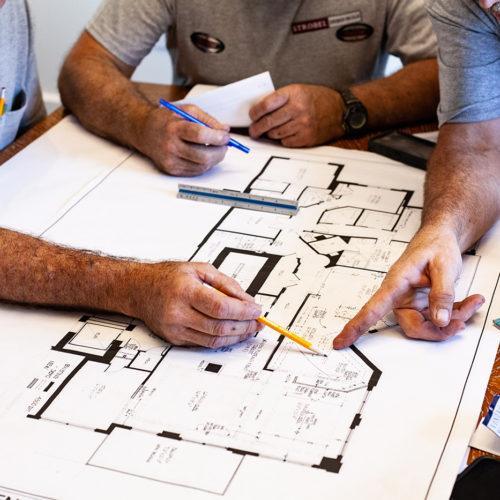 design build contractors in st. petersburg strobel team working on blueprint